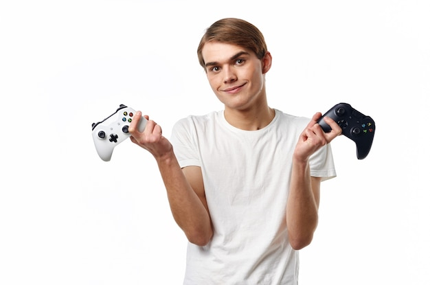 Man in witte t-shirt met joysticks in handen die entertainmenttechnologie spelen