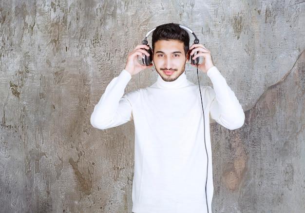 Man in witte trui koptelefoon dragen en luisteren naar de muziek.