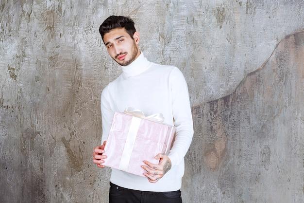 Man in witte trui met een paarse geschenkdoos omwikkeld met lint.