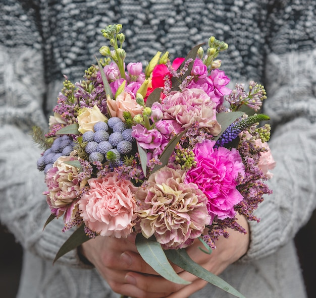 Man in wollen trui met een boeket van gemengde bloemen