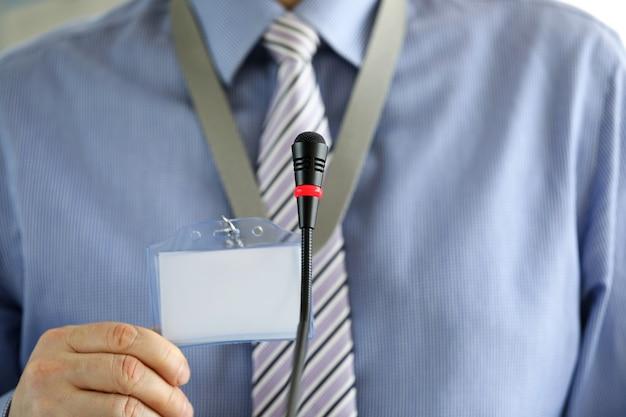 Man in zakelijke kleding voor een microfoon toont een badge. medewerker toont een document in het publiek