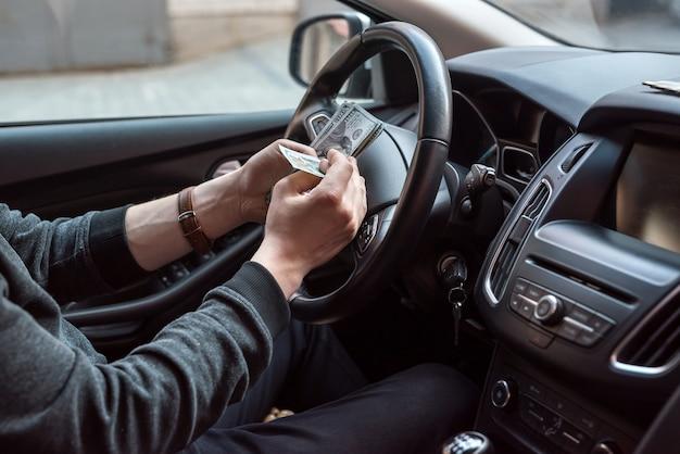 Man in zijn auto telt ons geld, rekeningen voor loon. financieel concept