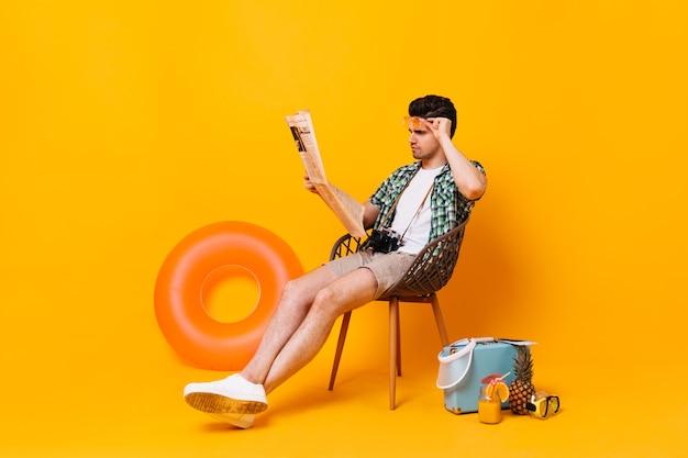Man in zomer outfit verwijdert bril en leest de krant. portret van man op oranje ruimte met koffer en rubberen ring.
