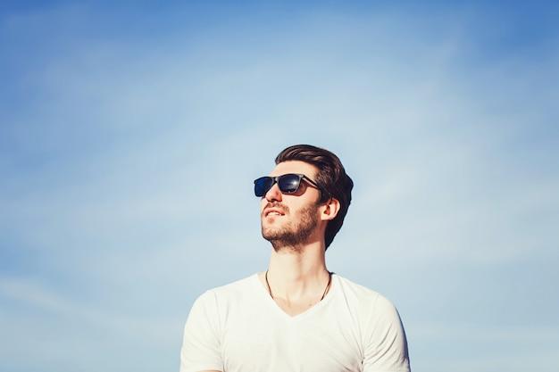 Man in zonnebril en t-shirt over blauwe hemel