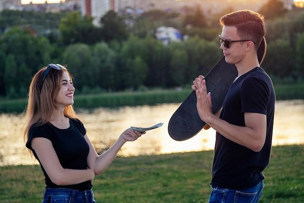 Man in zonnebril houdt een skateboard (longboard) vast en vrouw biedt geld aan bij zonsondergang op het strand. sportschaatsen kopen en verkopen op zomerpark