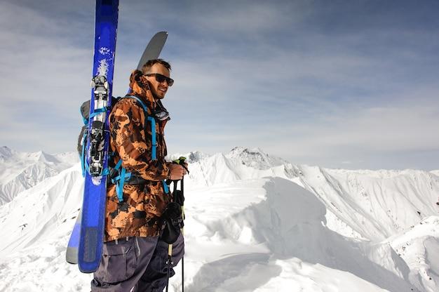 Man in zonnebril met ski en andere uitrusting staat op de top van de berg
