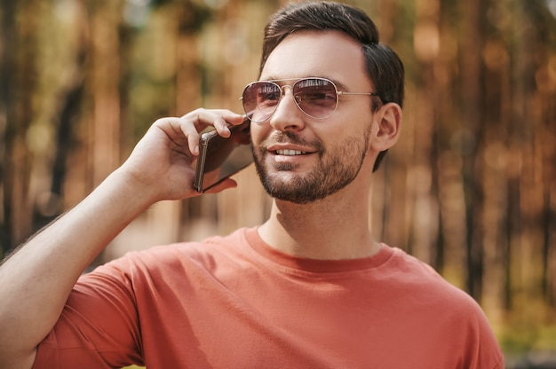 Man in zonnebril met smartphone in de buurt van oor