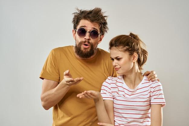 Man in zonnebril naast vrouw in gestreept t-shirt emoties communicatie mode studio plezier.