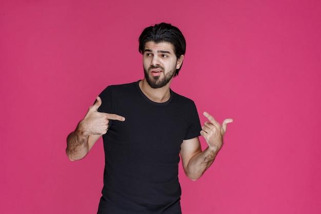 Man in zwart overhemd die op iets wijst of iemand introduceert