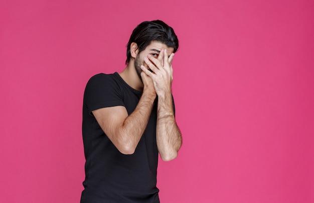 Man in zwart overhemd kijkt door zijn vingers