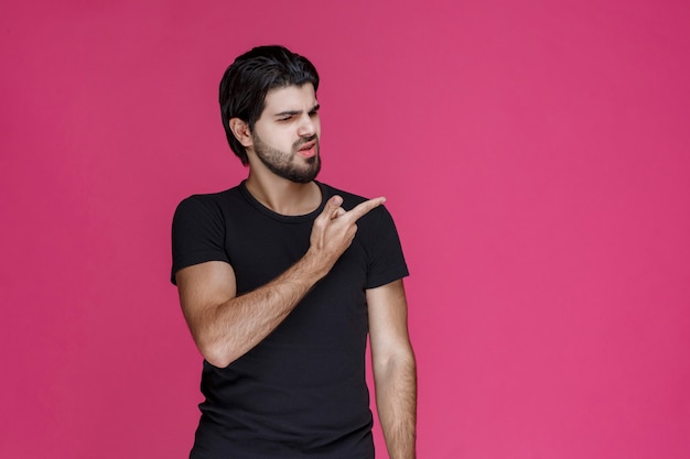 Man in zwart overhemd met baard die op een verwarde manier naar iets wijst of de richting aangeeft.