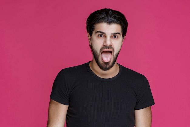 Man in zwart overhemd steekt zijn tong uit.