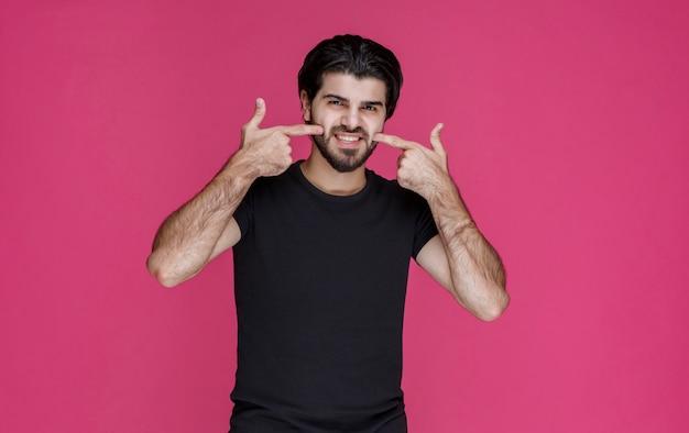 Man in zwart overhemd wijst op een vrolijk gezicht