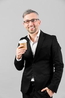 Man in zwart pak draagt een plastic beker