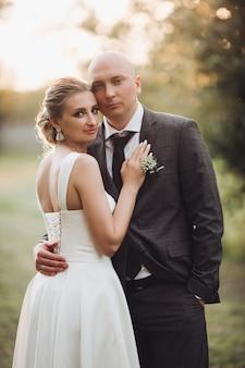 Man in zwart pak en wit overhemd knuffels met zijn mooie vrouw op de zonnige achtergrond buiten