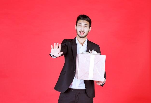 Man in zwart pak met een paarse geschenkdoos en iemand tegenhouden.