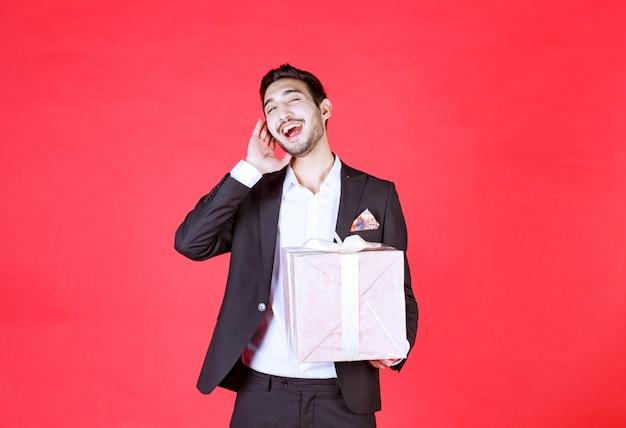 Man in zwart pak met een paarse geschenkdoos en schreeuwen.