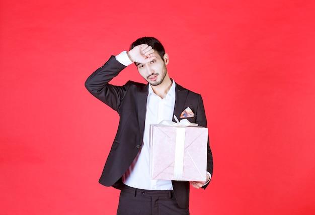 Man in zwart pak met een paarse geschenkdoos en ziet er moe en slaperig uit.