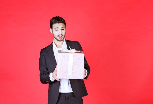 Man in zwart pak met een paarse geschenkdoos en ziet er verward en attent uit.