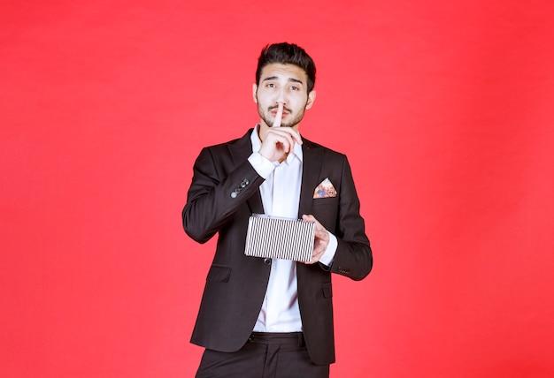 Man in zwart pak met een zilveren geschenkdoos en vraagt om stilte.
