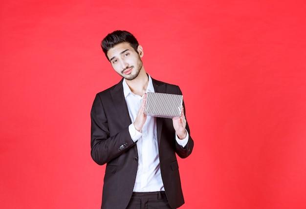 Man in zwart pak met een zilveren geschenkdoos en ziet er verward en attent uit.
