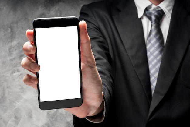 Man in zwart pak met slimme telefoon met leeg wit scherm op grijze grunge achtergrond