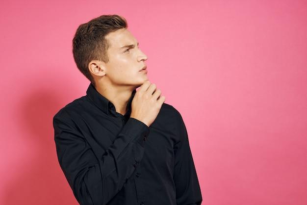 Man in zwart shirt gebaren met handen roze geïsoleerde ruimte.