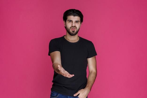 Man in zwart shirt geeft hand om iemand te begroeten en zijn hand te schudden
