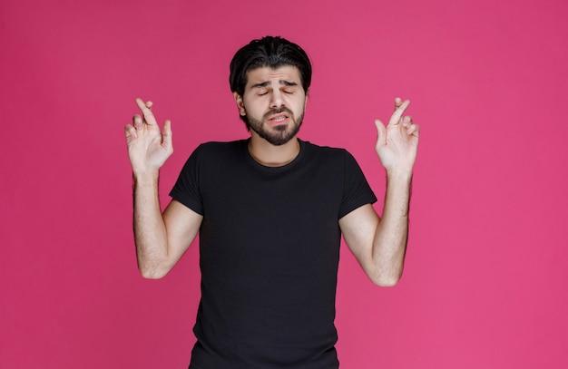 Man in zwart shirt hand dwarsteken maken