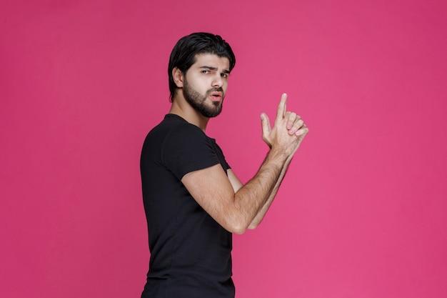 Man in zwart shirt hand pistool teken maken