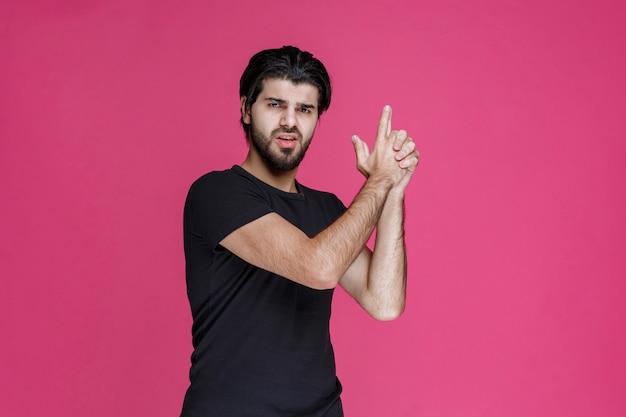 Man in zwart shirt handpistool symbool maken