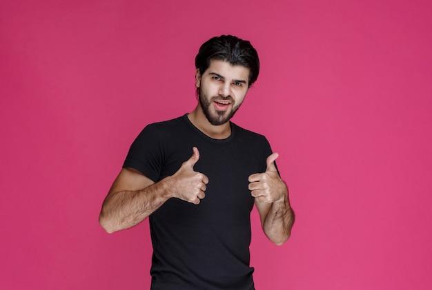 Man in zwart shirt laat zien dat hij helemaal van iets geniet