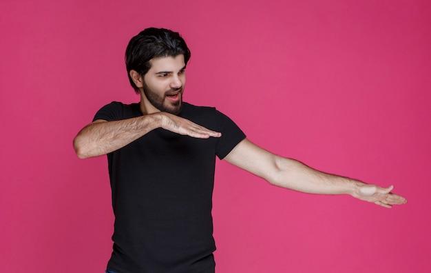 Man in zwart shirt voelt zich erg positief en heeft ergens van genoten