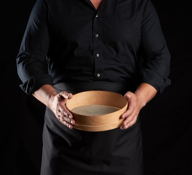 Man in zwart uniform met lege vintage ronde houten zeef voor het zeven van meel, chef-kok staat tegen zwarte achtergrond