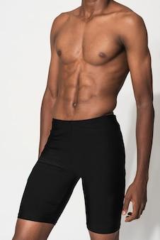 Man in zwarte compressieshort voor modeshoot in badmode