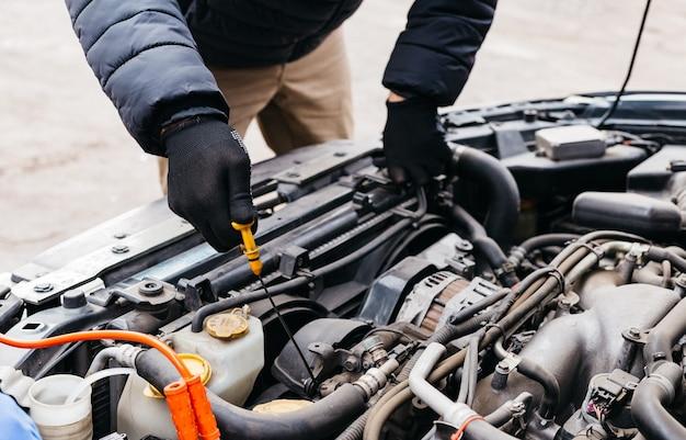 Man in zwarte handschoenen die het oliepeil in een auto buiten in de winter controleren.