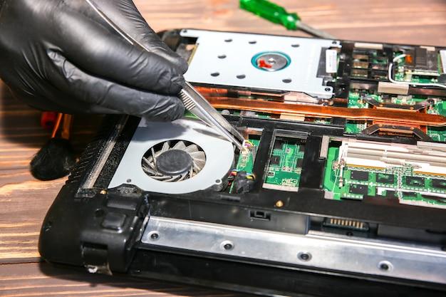 Man in zwarte handschoenen repareert een laptop. servicecentrummedewerker die het probleem oplost.