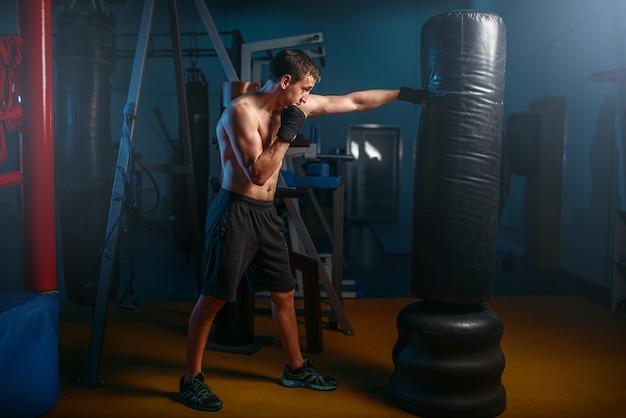Man in zwarte handwraps oefeningen met tas in de sportschool