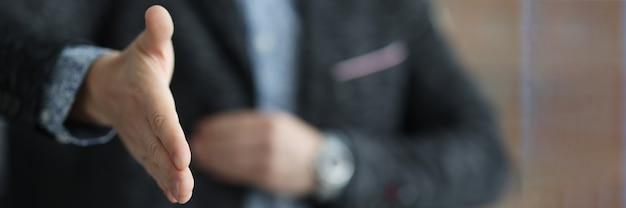 Man in zwarte jas die zijn hand uitstrekt voor handdruk close-up