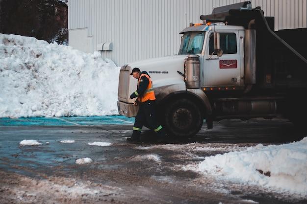 Man in zwarte jas en groene broek staande naast witte vrachtwagen overdag