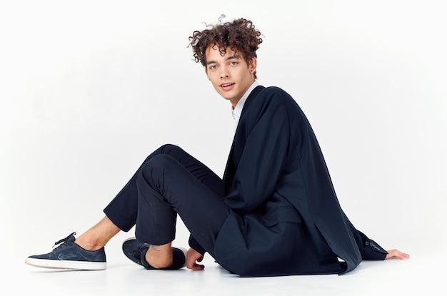 Man in zwarte jas moderne stijl krullend haar leuke emoties mode