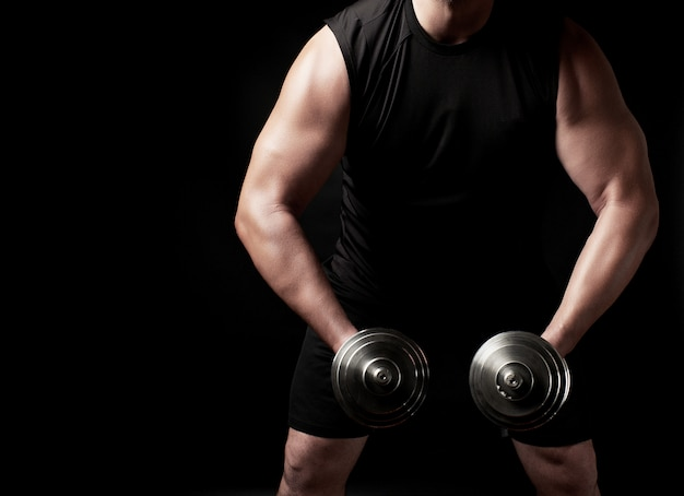 Man in zwarte kleding houdt stalen halters in zijn handen, zijn spieren zijn gespannen
