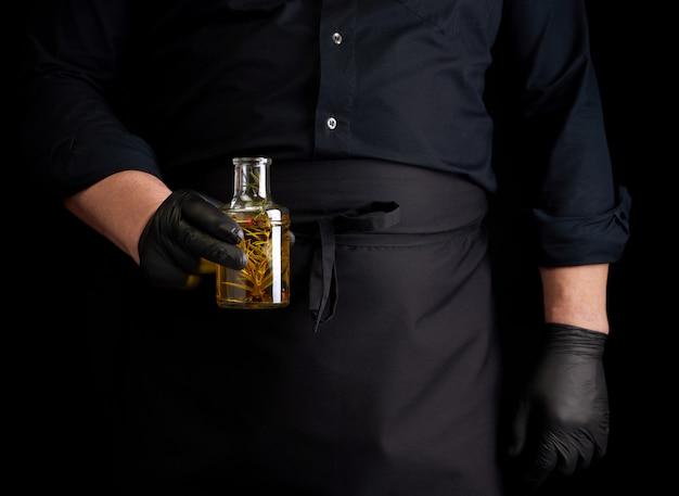 Man in zwarte kleding, latex handschoenen houdt een doorzichtige fles met olijfolie