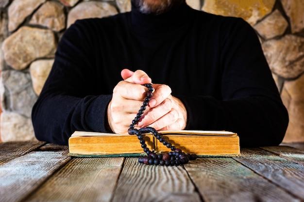 Man in zwarte kleding met een rozenkrans in zijn handen