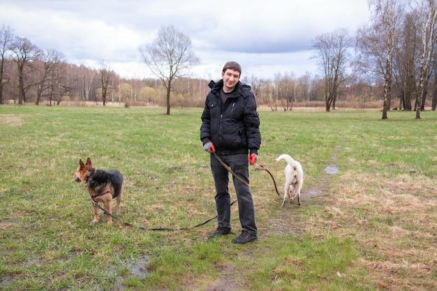 Man in zwarte kleren met twee honden aan de leiband die op groen grasveld staan