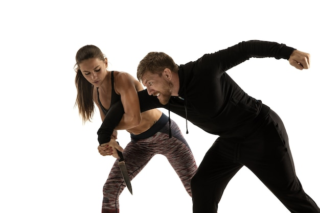 Man in zwarte outfit en atletische blanke vrouw vechten op witte studio achtergrond. zelfverdediging, rechten, gelijkheid van vrouwen. tegengaan van huiselijk geweld of diefstal op straat.