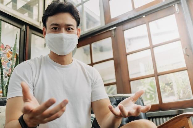 Man influencer met masker praat met zijn camera in een café