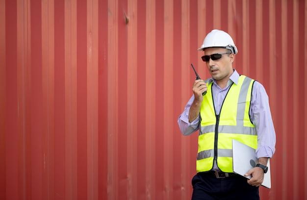 Man ingenieur met walkie-talkie in scheepswerf, industriële werknemer controleert container laden door walkie talkie in import-export bedrijf.