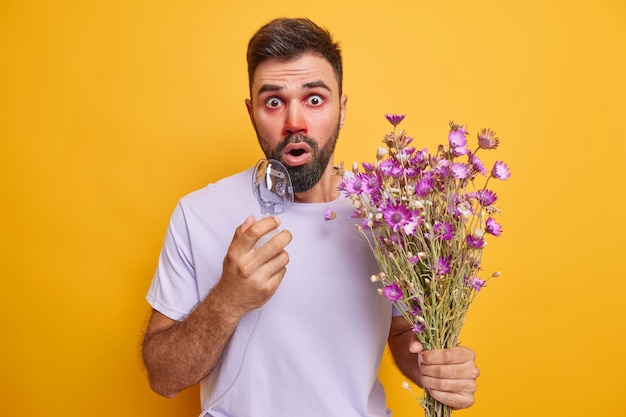 Man inhaleert zuurstofmasker gebruikt allergisch voor wilde bloemen voelt zich onwel heeft rode waterige ogen jeukende neus staart geschokt naar camera draagt t-shirt geïsoleerd op geel