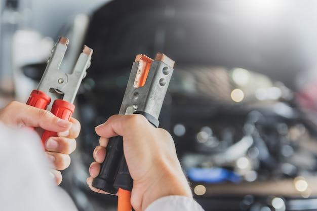 Man inspectie bedrijf jumper kabels voor lader batterij service onderhoud van industriële naar motor reparatie. in fabriek transport auto automotive afbeelding